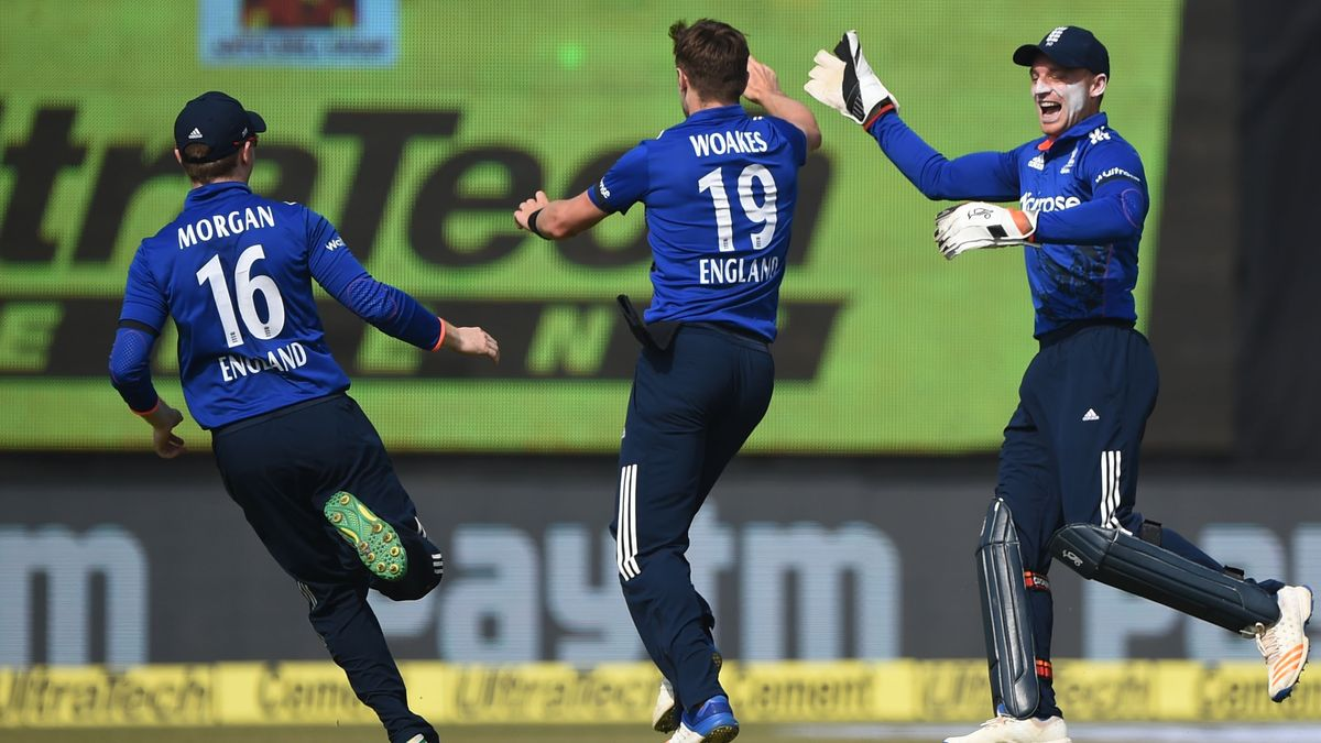 Eoin Morgan, Chris Woakes and Jos Buttler celebrate a wicket on their ODI tour of India
